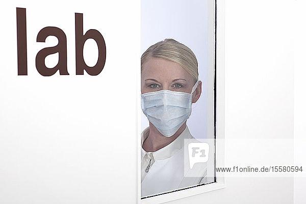 Arzt schaut durch Labortür