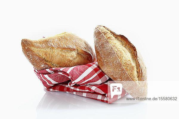 Baguette-Rolle mit Küchentuch auf weißem Hintergrund