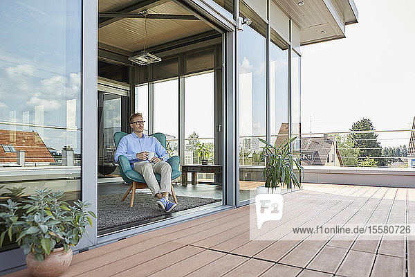 Young man sitting in armchair at balcony door
