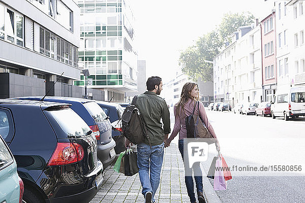 Germany  Cologne  Young couple with shopping bags near parking lot  smiling