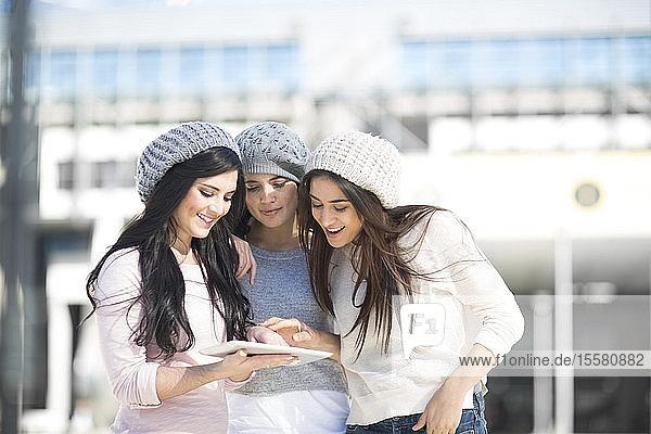Drei Freundinnen mit Wollmützen mit digitalem Tablett