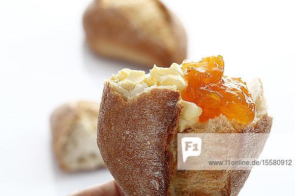 Baguettebrötchen mit Butter und Marmelade auf weißem Hintergrund