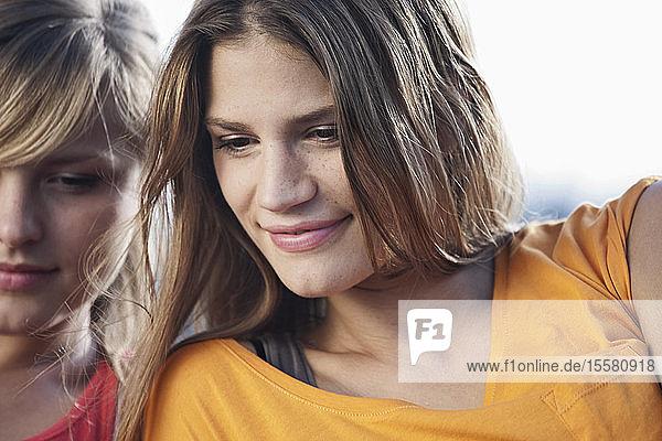 Deutschland  Köln  Junge Frau schaut nach unten  lächelt