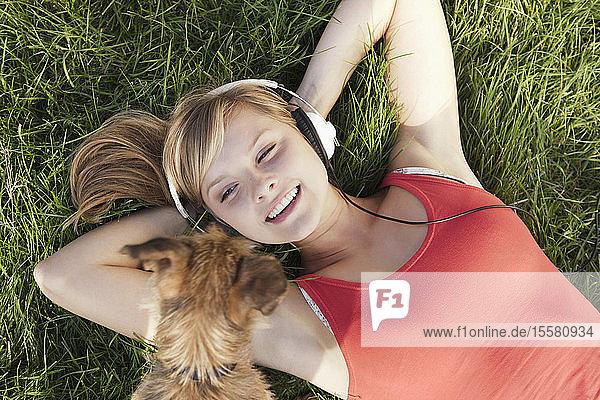 Deutschland  Köln  Junge Frau mit Hund im Gras liegend  lächelnd