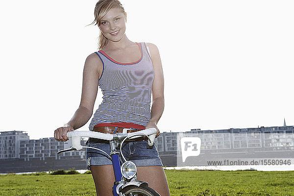 Deutschland  Köln  Junge Frau mit Fahrrad  lächelnd  Portrait