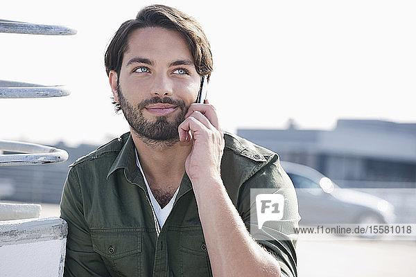 Deutschland  Köln  Junger Mann am Telefon  lächelnd