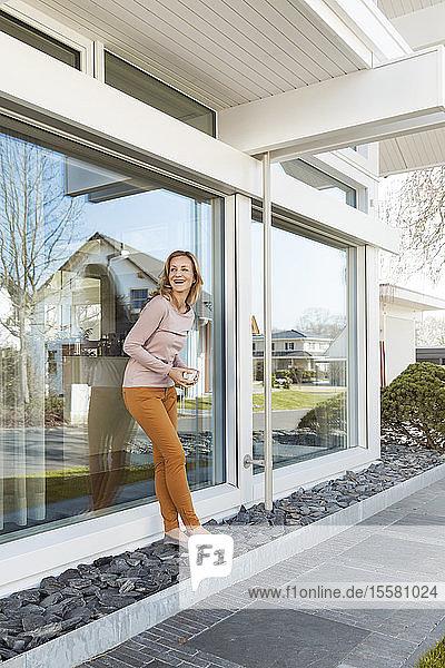 Lächelnde Frau lehnt vor dem Wohnhaus