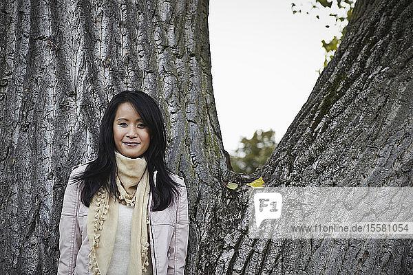 Deutschland  Köln  Junge Frau am Baumstamm im Park  lächelnd  Porträt