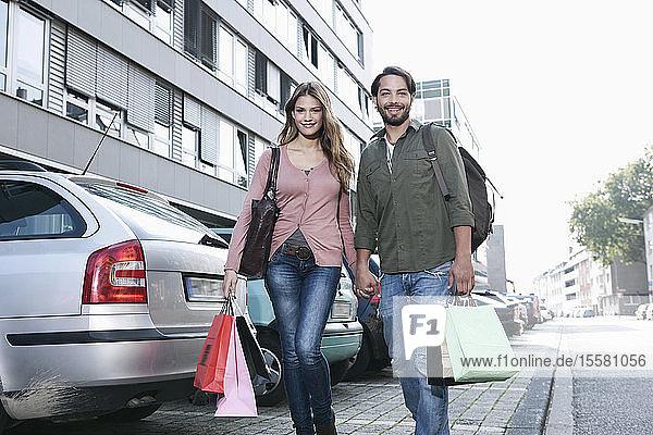 Deutschland  Köln  Junges Paar mit Einkaufstaschen in der Nähe des Parkplatzes  lächelnd