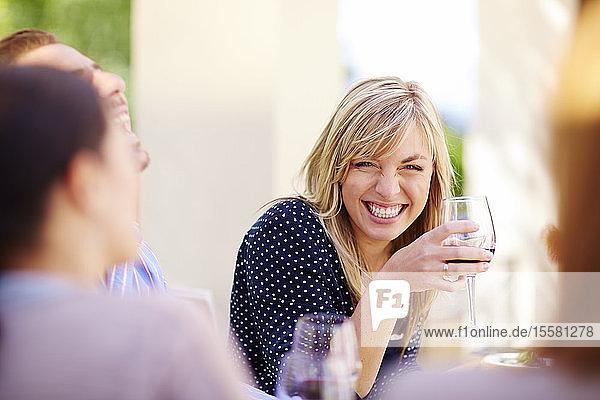 Glückliche Freunde mit Rotweingläsern im Freien