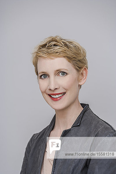 Porträt einer lächelnden blonden Frau vor grauem Hintergrund