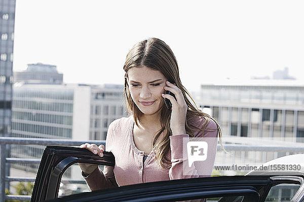 Deutschland  Köln  Junge Frau am Telefon in der Nähe des Parkplatzes  lächelnd