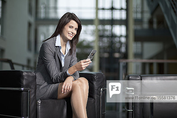 Deutschland  Bayern  Geschäftsfrau mit Handy  lächelnd  Portrait