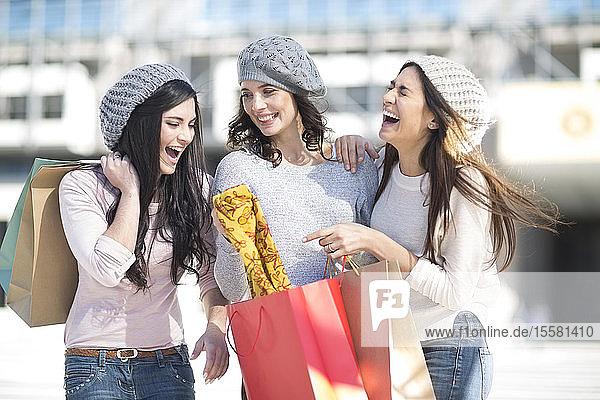 Drei Freundinnen mit Wollmützen und Einkaufstaschen