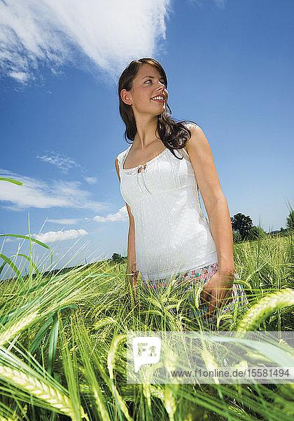 Deutschland  Junge Frau in einem Weizenfeld  lächelnd