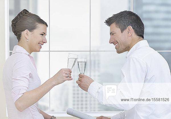 Geschäftsfrau und Mann feiern mit Champagner im Büro und lächeln