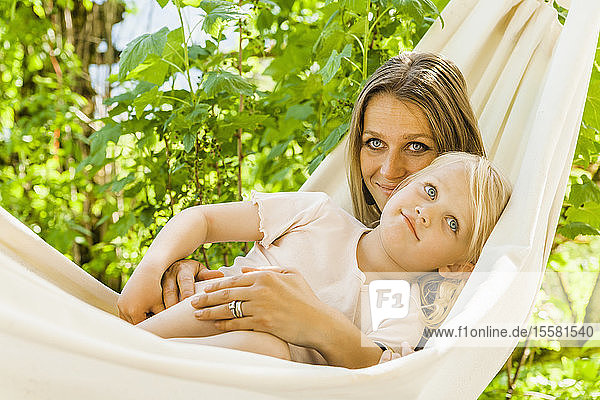 Mother and daughter relaxing in hammock