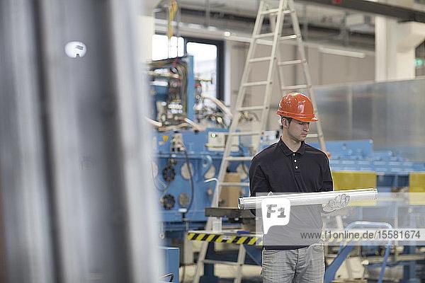 Junger Techniker trägt Rohre in Industriehalle