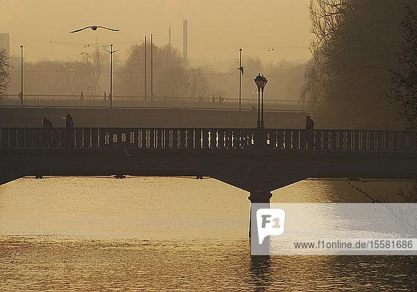 Deutschland  München  Blick auf die Brücke über die Isar bei Sonnenuntergang