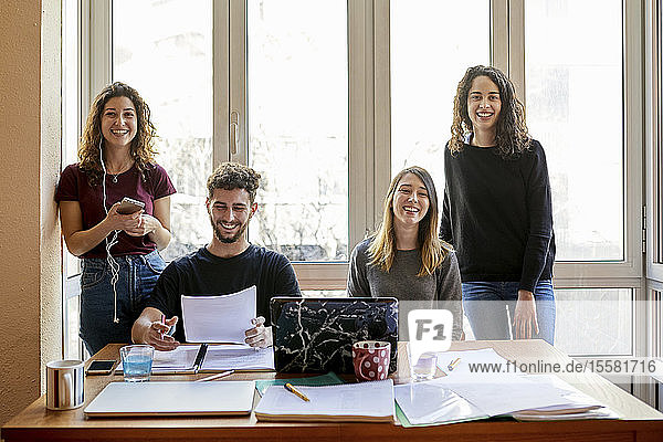 Portrait of four happy students at desk and at the window