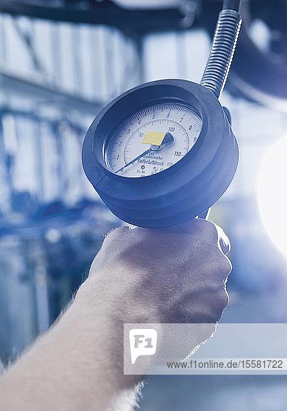 Deutschland  Augsburg  Menschliche Hand misst Luftdruck in Reifen