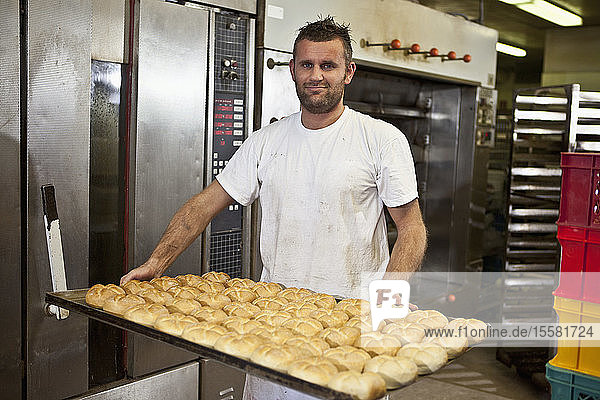 Germany  Bavaria  Munich  Baker holding tray full of bread rolls  portrait