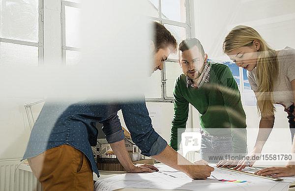 Drei junge Architekten im Büro diskutieren über