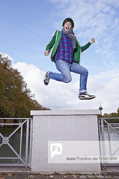 Deutschland,  Köln,  Junger Mann springt auf Brücke,  Porträt