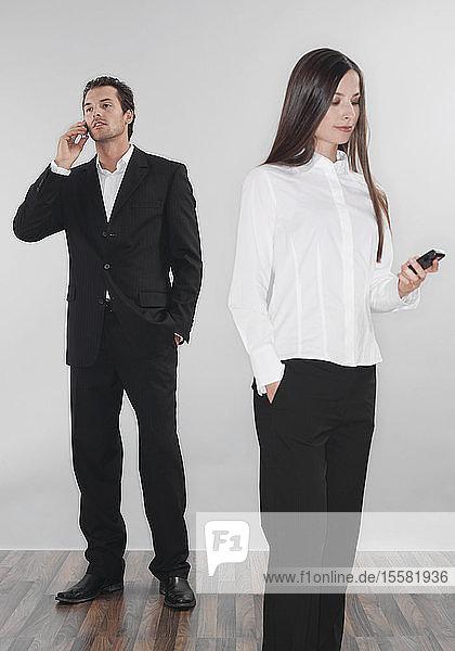 Geschäftsfrau und Mann benutzen Mobiltelefone