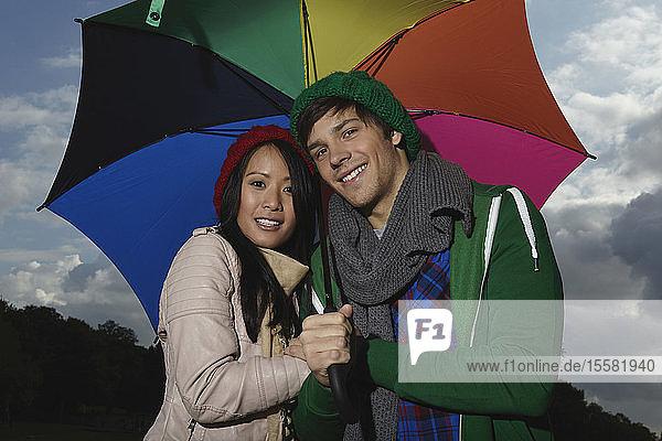 Deutschland,  Köln,  Junges Paar mit Regenschirm im Park,  lächelnd,  Porträt