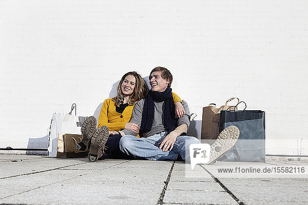 Germany  Bavaria  Munich  Young couple with shopping bag  smiling