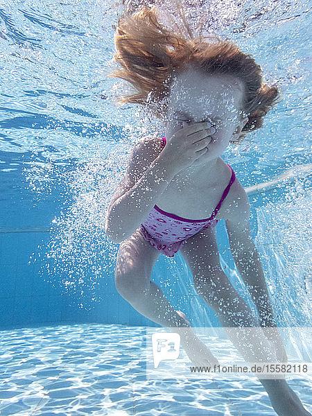 Kleines Mädchen unter Wasser im Schwimmbad