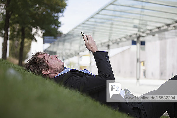 Businessman lying on a meadow using his smartphone