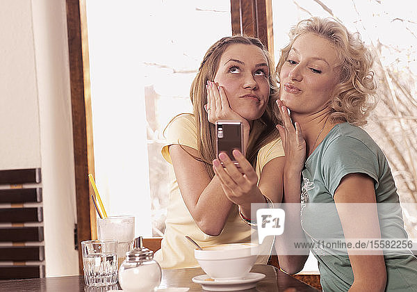 Germany  Augsburg  Two young women taking self portrait using mobile phone