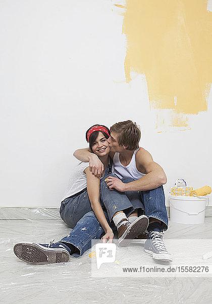 Junges Paar streicht neues Haus  lächelt