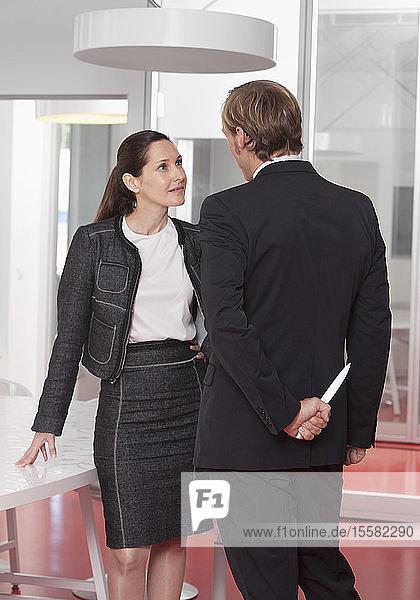 Geschäftsmann spricht mit Frau und hält Messer hinter seinem Rücken