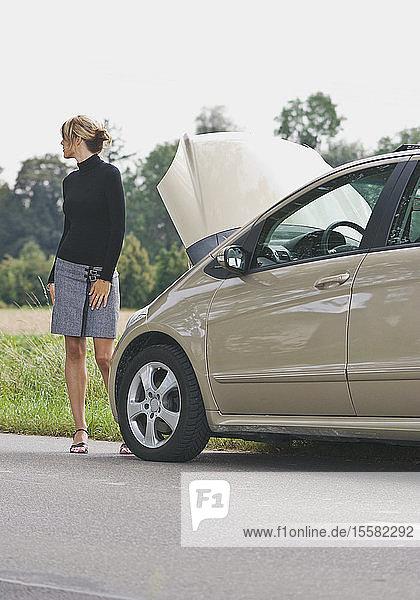 Deutschland  Augsburg  Junge Frau steht am Abschleppwagen