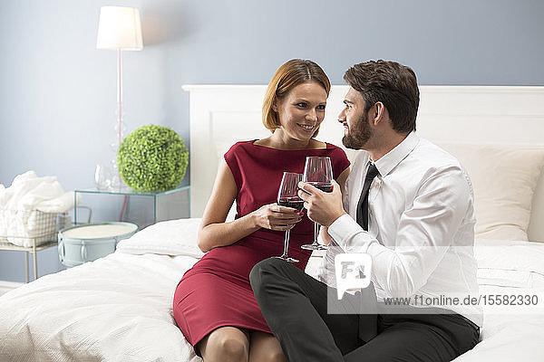 Liebespaar hält Weingläser im Schlafzimmer