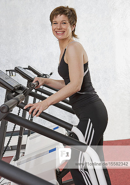 Deutschland  München  Junge Frau auf dem Laufband im Fitnessstudio  Portrait