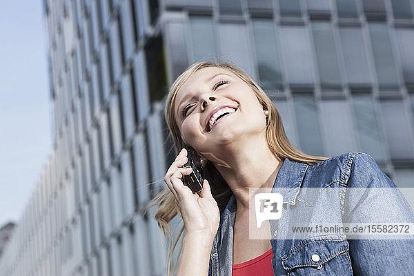 Deutschland  Köln  Junge Frau am Telefon  lächelnd  Porträt
