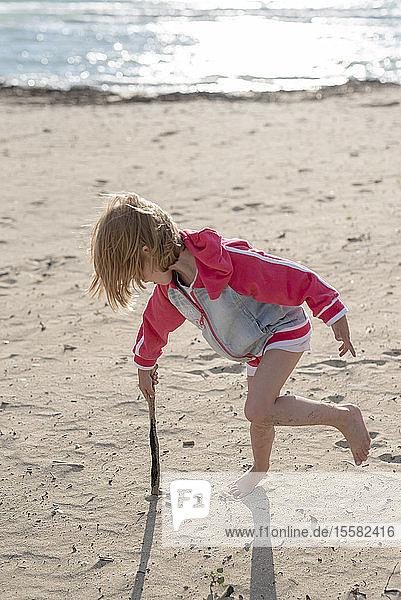 Griechenland  Parga  kleines Mädchen spielt mit einem Stock am Strand