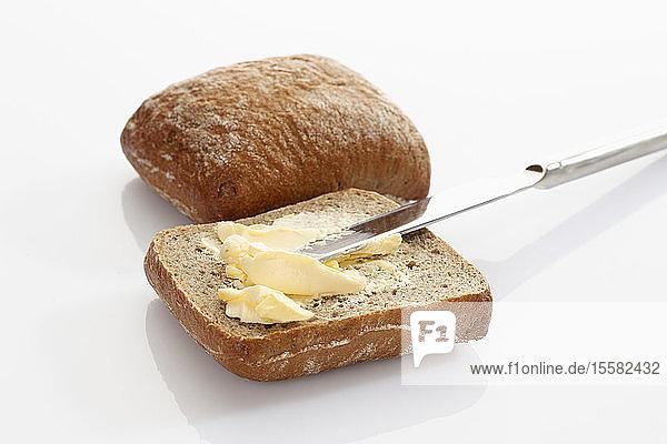 Brot mit Butter und Messer auf weißem Hintergrund