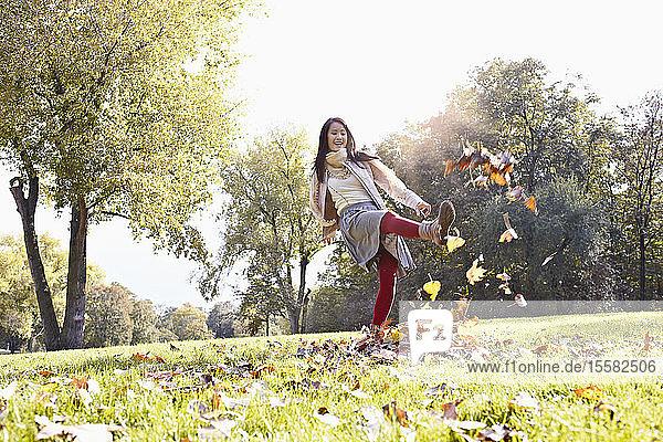 Deutschland  Köln  Junge Frau spielt im Park mit Blättern  lächelnd