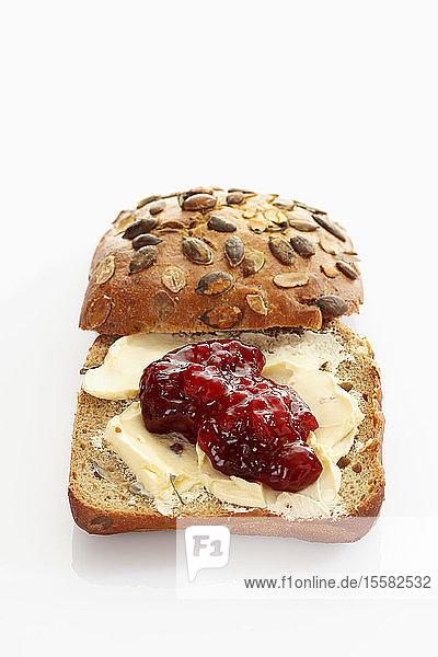 Vollkornbrot mit Butter und Marmelade auf weißem Hintergrund