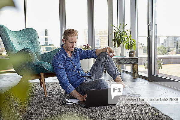 Young man sitting on carpet at home using laptop
