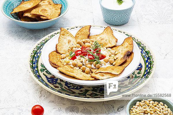 Nahaufnahme von Fatteh auf dem Teller mit Minzjoghurt in der Schale