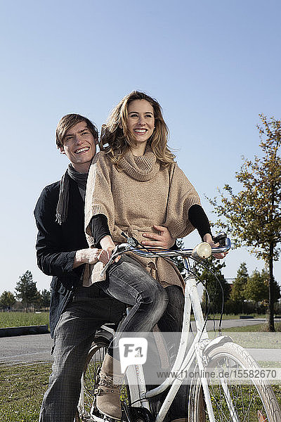 Germany  Bavaria  Munich  Young couple on bike  smiling