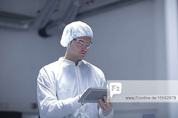 Techniker im Reinraum mit digitalem Tablett
