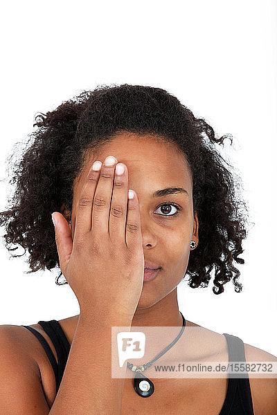Porträt einer jungen Frau  die mit ihrer Hand die Hälfte des Gesichts bedeckt