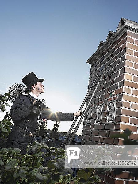 Deutschland  Schornsteinfeger mit Besen auf der Leiter